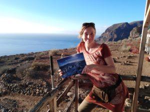 """Barbara Focke steht an der Ecke der kleinen Aussichtsplattform. In ihren Händen hält sie das Buch """"Die Insel der Delfine"""". Im Hintergrund sieht man wieder das Meer und die Berge von La Gomera"""