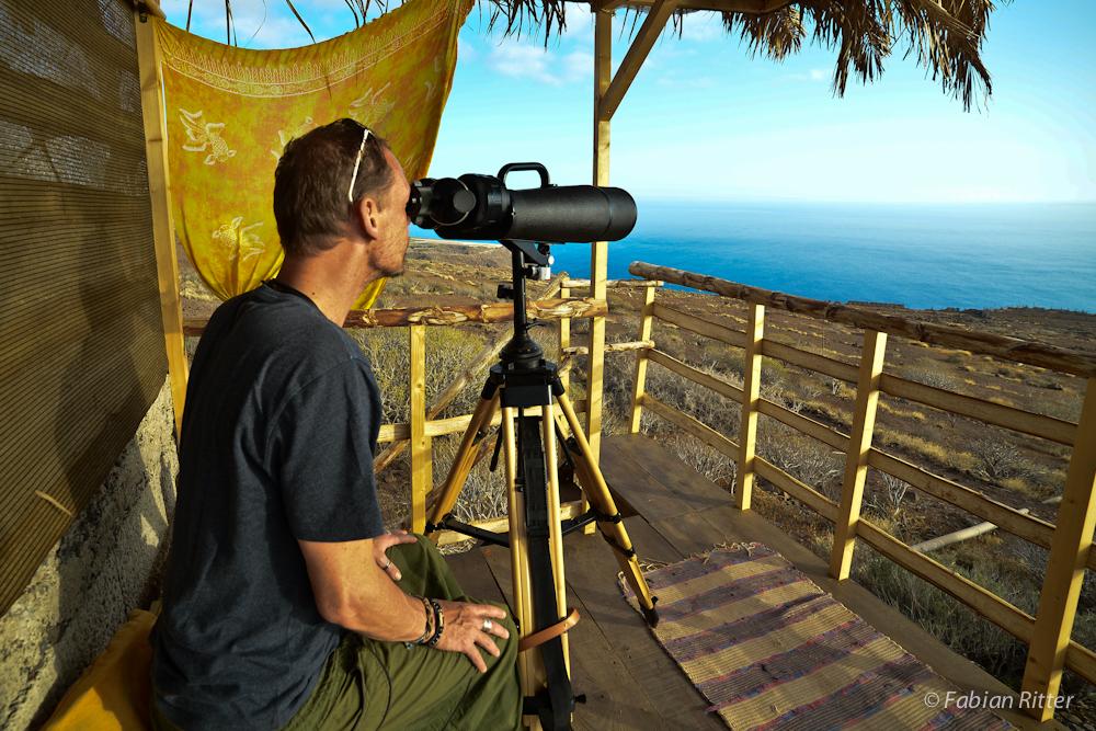 Der Autor Fabian Ritter sitzt auf der Aussichtsplattform auf La Gomera. Er blickt durch ein großes Teleskop. Im Hintergrund sieht man das endlose Meer, auf das das Teleskop gerichtet ist