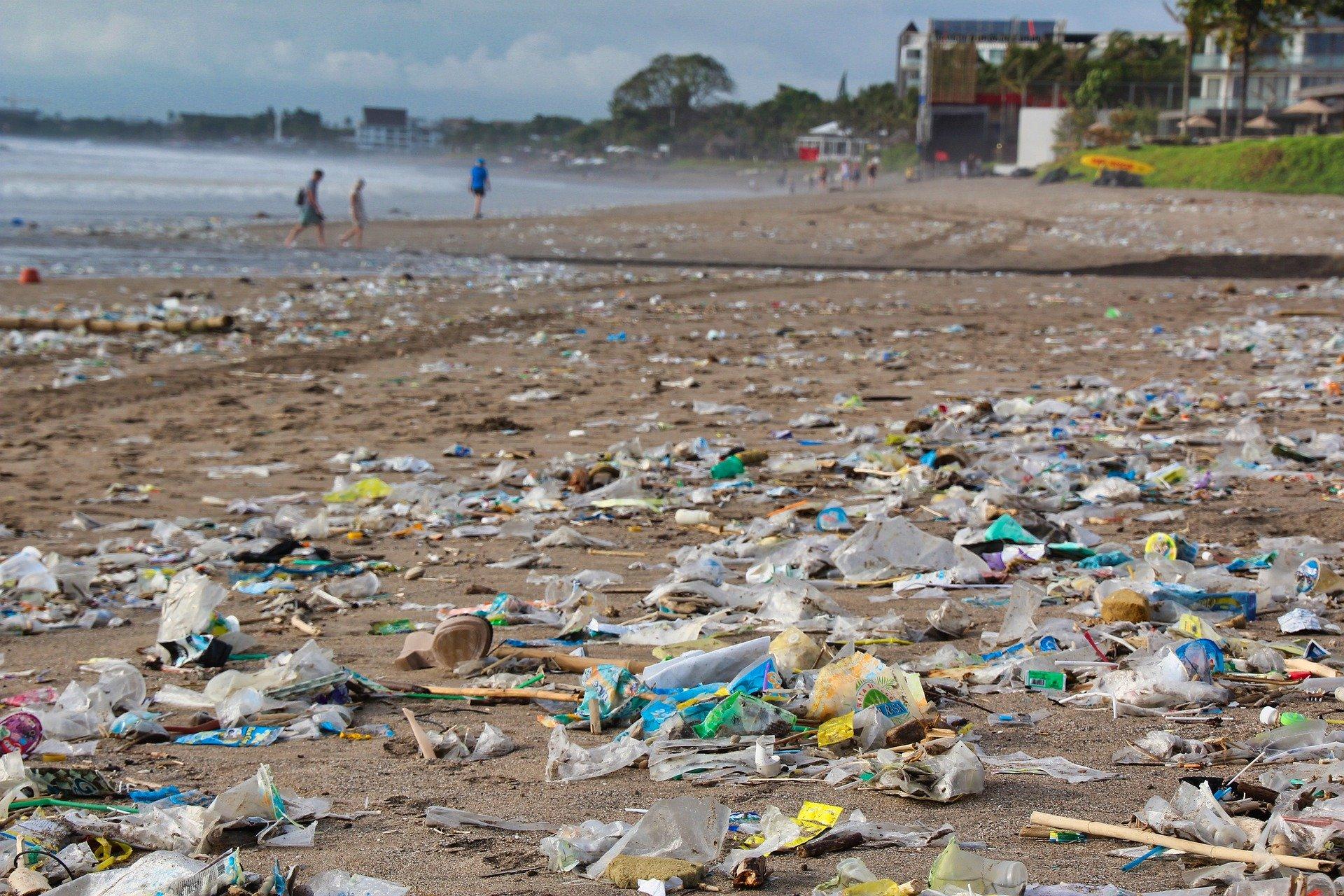 Sehr viel Plastikmüll liegt an einem Strand. Man kann kaum gehen, ohne auf Plastik zu treten. Im Hintergrund laufen ein paar Menschen. Rechts im Hintergrund ist ein Hotel zu sehen. Tourismus ist eines der Probleme, das der Runde Tisch Meeresmüll bespricht.