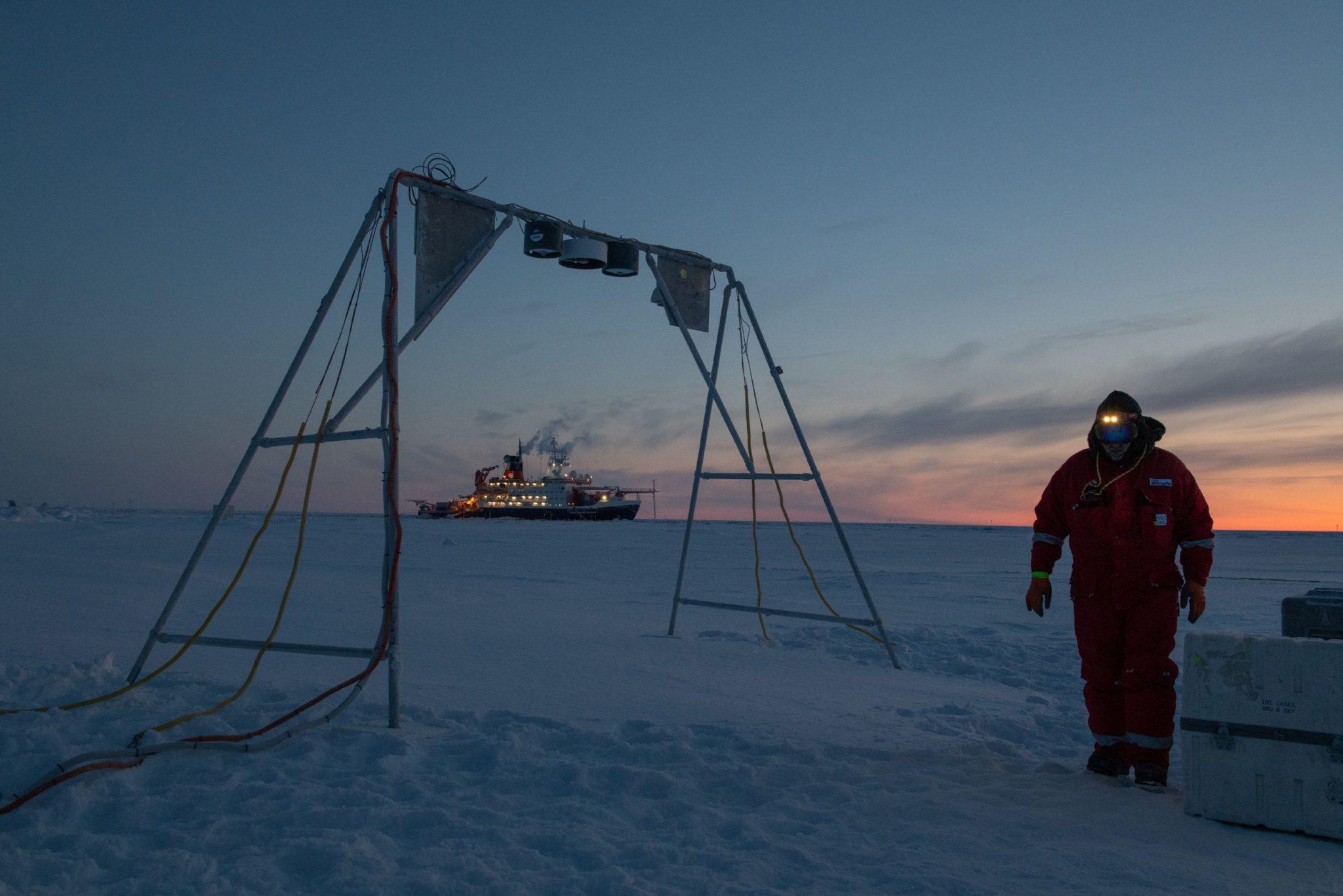 Ein Mann läuft auf einer dicken Eisdecke entlang, im Hintergrund ist ein großes Forschungsschiff zu sehen