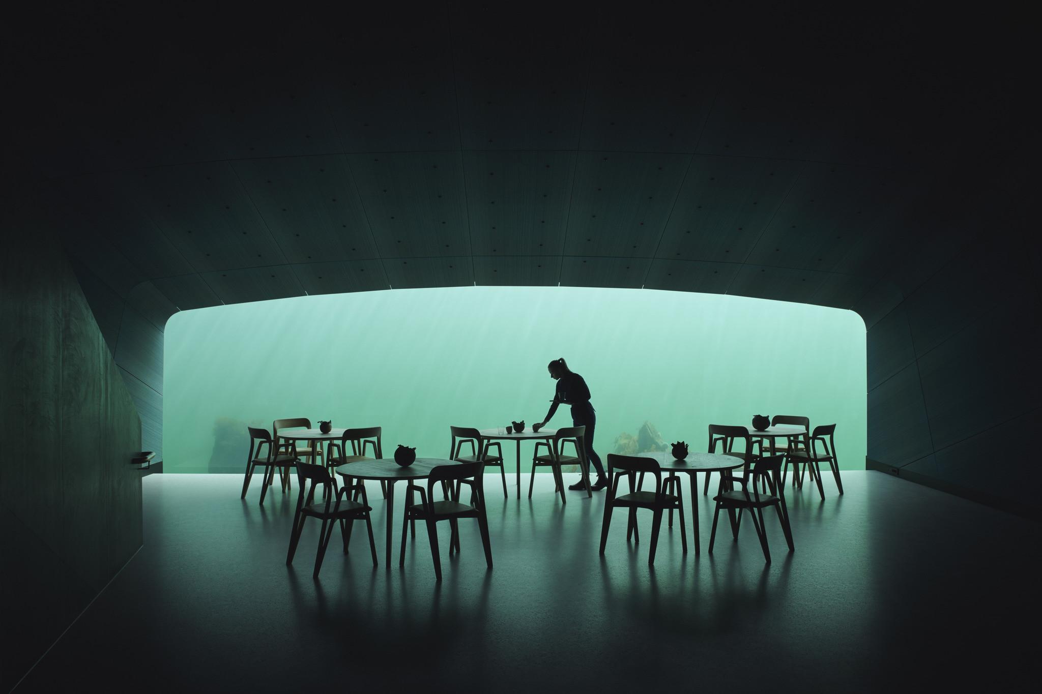 Das Bild zeigt mehrere Tische mit fühlen in einem Speisesaal. Im Hintergrund ist eine große Fensterfront durch die man ins offene Meer schauen kann.