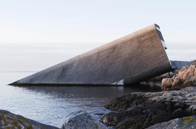 Das Bild zeigt ein Restaurant aus Betonwänden welches schräg aus dem Ozean heraus ragt. Das Restaurant befindet sich an der Küste und ist halb im Wasser versunken.