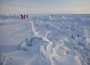 Forscher:innen in roten Anzügen stehen mitten in Schnee und Eis