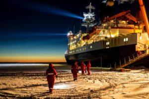 Der Eisbrecher Polarstern ist in einer arktischen Scholle eingefroren. Die Forscher und Forscherinnen gehen, in roten Thermoanzügen, auf der schneebedeckten Scholle umher. Es ist dunkel, nur im Horizont sieht man den rötlichen Schein der Sonne.