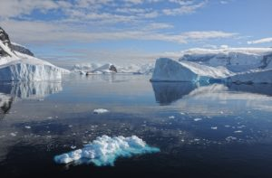 Zu sehen ist die Antarktis. Im Vordergrund ist Schnee, der im Meer schwimmt, im Hintergrund sind antarktische Gletscher zu sehen.