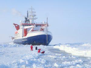 Ein Forscher steht mit rotem Anzug mitten im Eis vor dem großen Schiff Polarstern