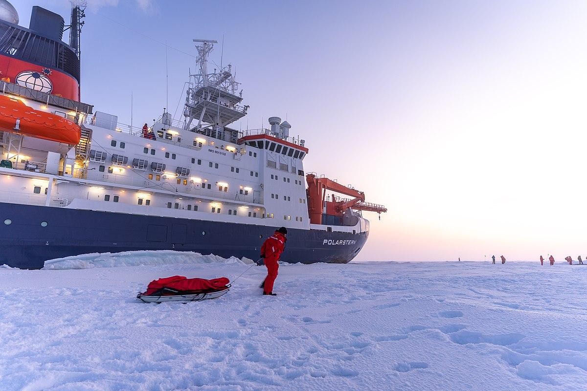 Forschungsschiff Polarstern, fest gefroren in Eisscholle. Es ist Tag und man sieht Forscher und Forscherinnen auf dem Schiff und am Horizont. Vor dem Schiff zieht ein Forscher einen Schlitten mit einer roten Plane.