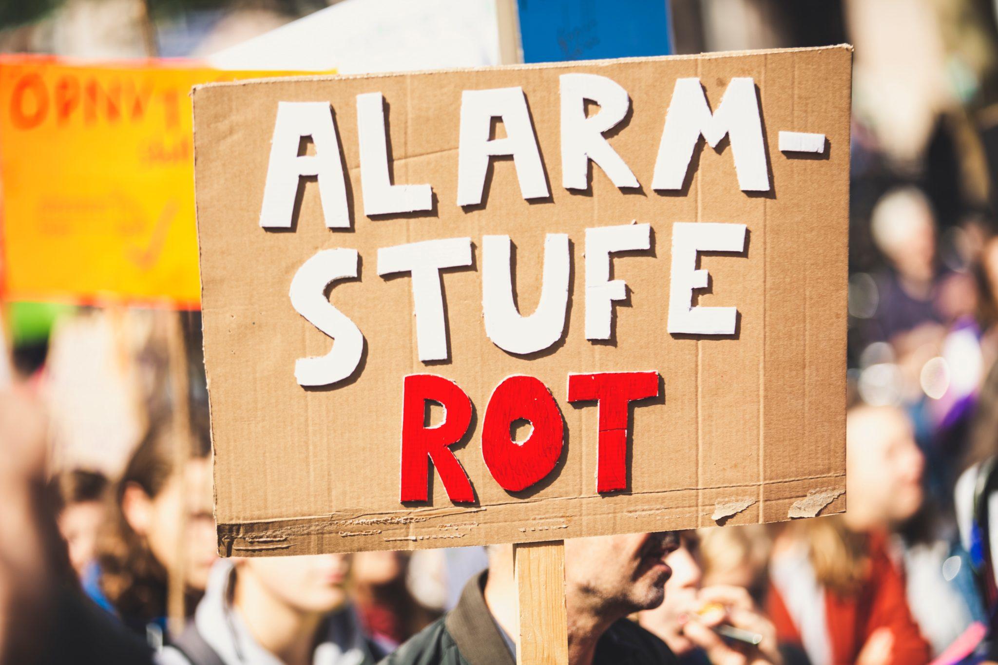 """Ein Pappschild mit der Aufschrit """"Alarmstufe Rot"""" ist im Vordergrund. Es wird von einem Demonstranten hochgehalten."""