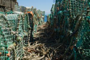 Gestapelte Fischnetzfallen an Land, mit herumliegenden Tauen und schmalem Blick aufs Meer
