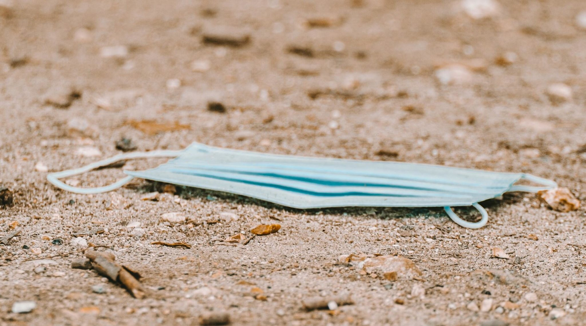 Mund-Nasen-Maske als angespülter Müll im Sand
