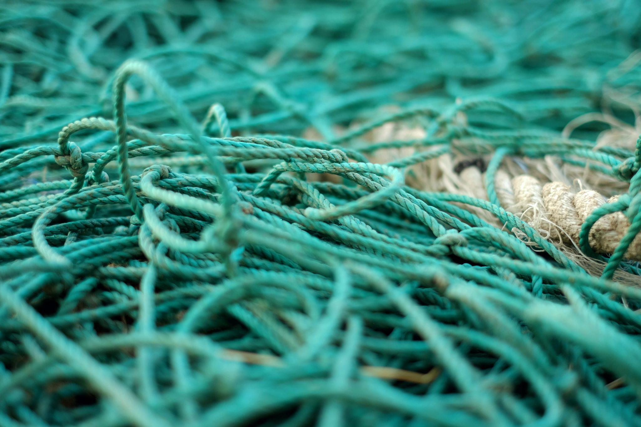 Nahaufnahme eines Fischereinetzes in grün-blau