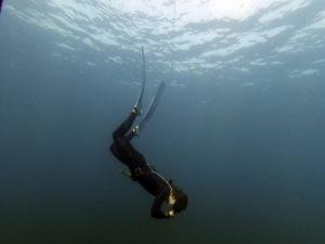 Apnoetaucherin, die nach unten schwimmt und einen Druckausgleich macht.