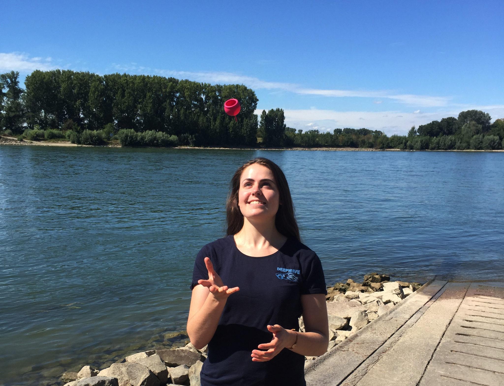 Eine Frau mit blauem DEEPWAVE T-Shirt steht lachend am Rheinufer und wirft eine pinke Tasse (Menstruationscup) in die Luft, die ihr in die geöffnete Hand fallen wird.