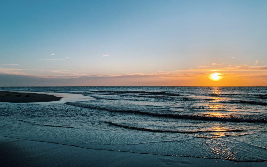 Aufnahme des Sonnenuntergangs an der dänischen Nordsee. Die Sonne verschwindet bald hinter dem Horizont und spiegelt sich schön auf dem Wasser