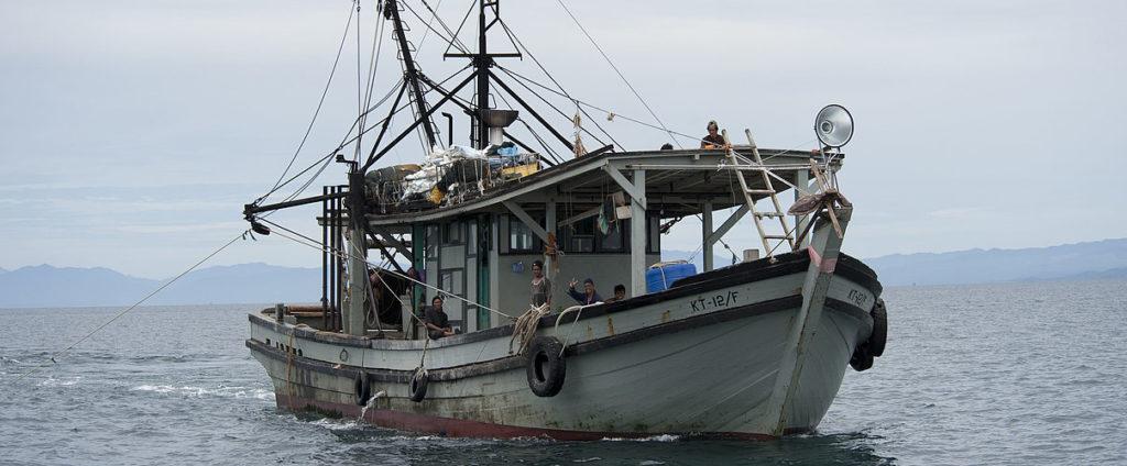 Weltbank Profish: Ein schäbig aussehendes Schifferboot fährt mit Besatzung über das Meer. Im Hintergrund an der Küste sind Berge zu sehen