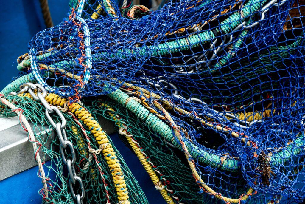 Ein mehrfarbiges Schleppnetz hängt über die Reling eines blauen Schiffes. Mehrere Seile, Tampen und Ketten liegen übereinander