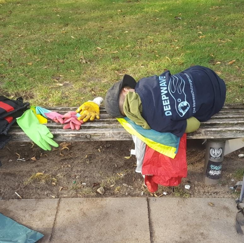 Kleiner Junge liegt erschöpft auf einer Bank und schläft, nachdem er Müll gesammelt hat. Gummihandschuhe liegen neben ihm, er trägt ein DEEPWAVE T-Shirt.