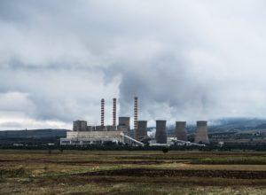 Ein großes Atomkraftwerk steht auf einem trockenen, braunen Feld. Der Dampf weht in den grauen Himmel.