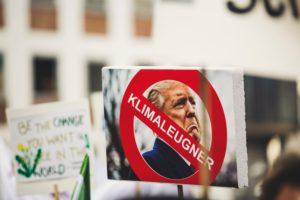 """Ein Protestschild, auf dem Trumps Gesicht zu sehen ist, über dem ein rotes Warnschild mit der Schrift """"Klimaleugner"""" gedruckt ist."""""""
