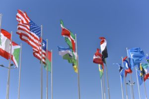 Mehrere Flaggen verschiedener Länger wehen im Wind, der Himmel ist blau.