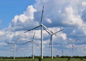 Mehrere Windräder stehen auf einem flachen Feld vor blauem Himmel mit Wolken