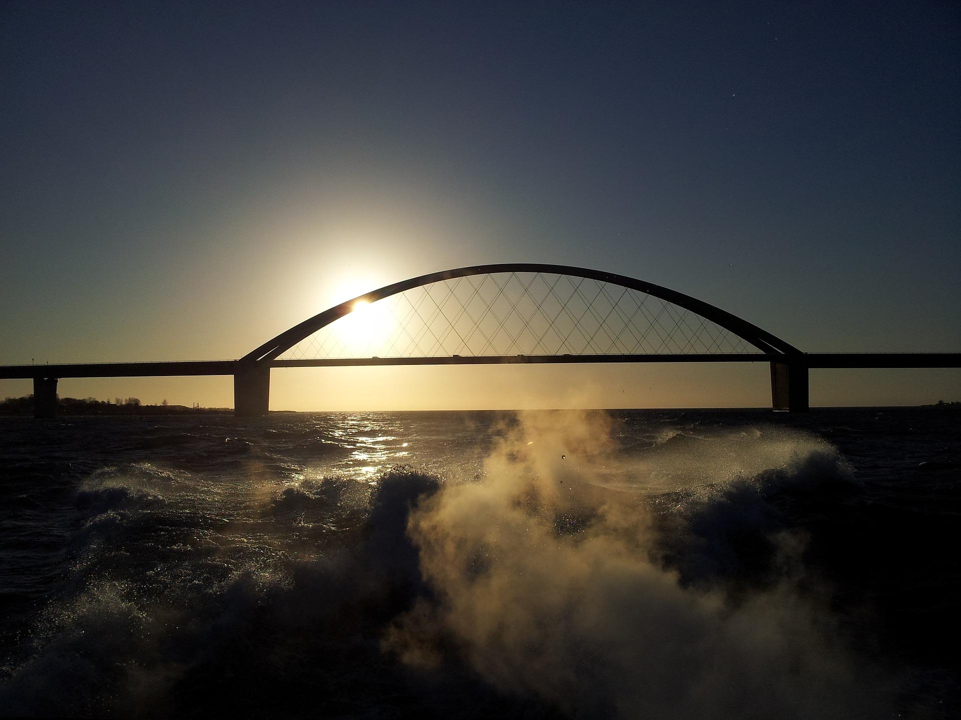 Vor der untergehenden Sonne sieht man die Brücke nach Fehmarn, im Vordergrund Wellen