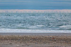 Vom Strand aus sieht man in der Ferne auf dem offenen Meer einen großen Offshore-Windpark
