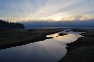 Ein Fluss mündet ins offene Meer, es ist Sonnenaufgang und die Sonne spiegelt sich im Wasser