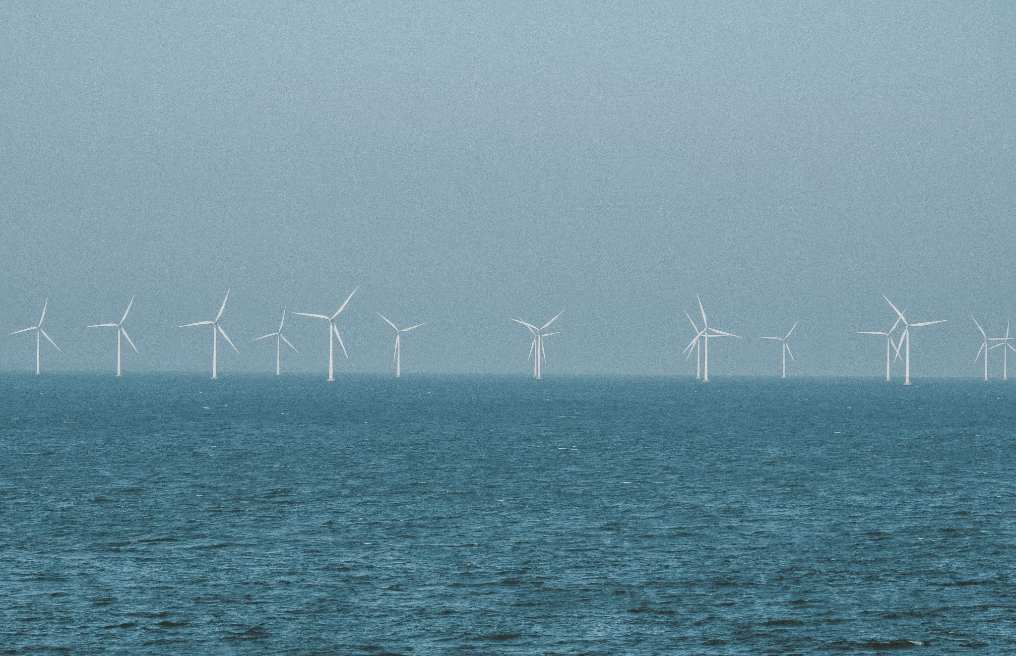 Viele Windräder stehen in der Ferne im Meer, das Wetter sieht stürmisch aus