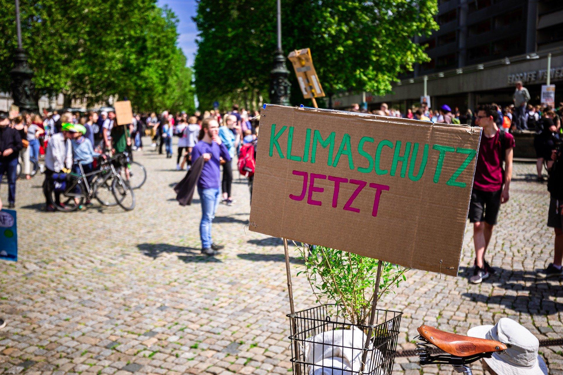 """Auf einer Demonstration steht ein Fahrrad mit einem Pappschild auf dem """"Klimaschutz jetzt"""" steht"""