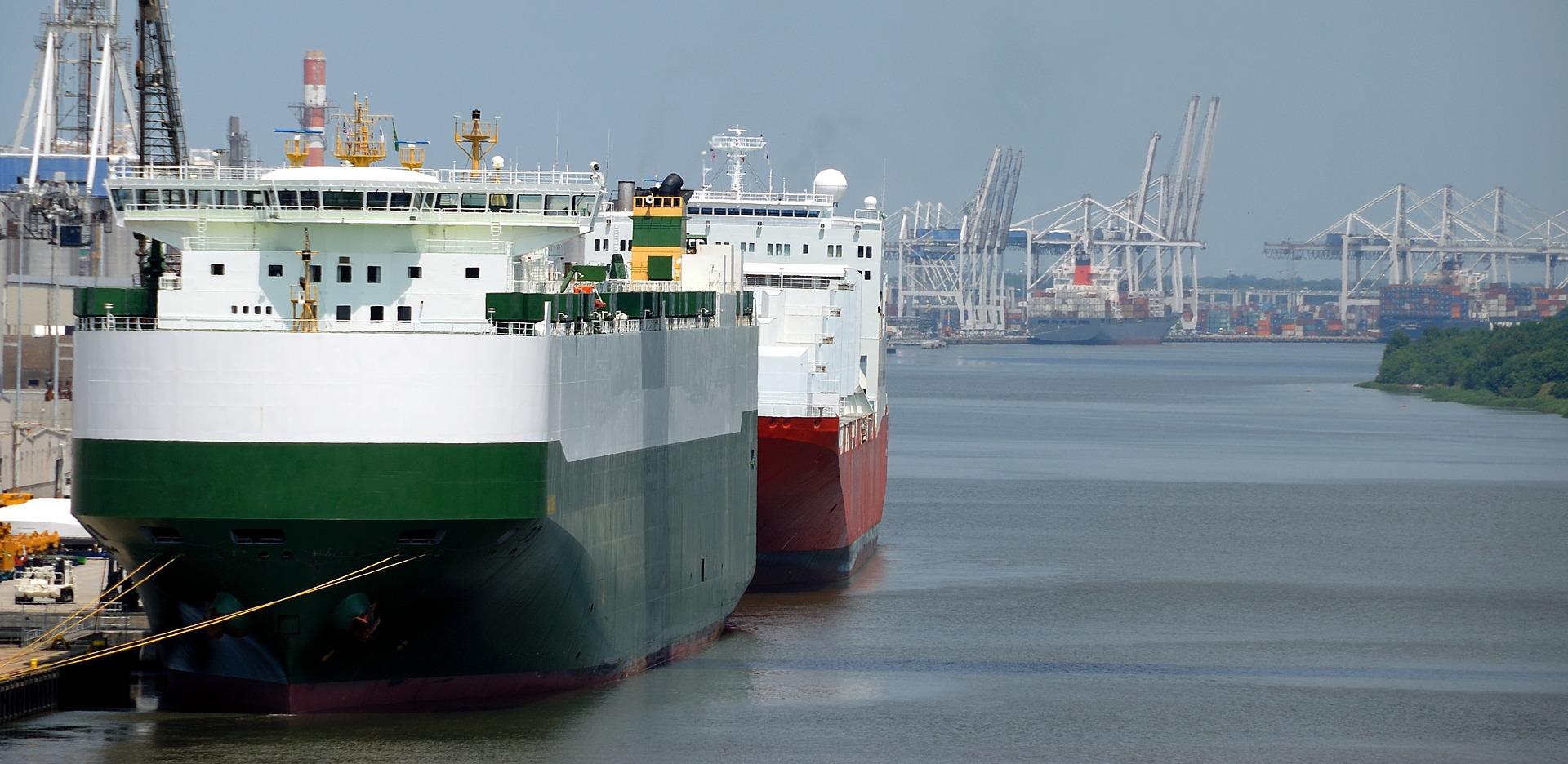 Zwei Frachter liegen auf dem Wasser, im Hintergrund sieht man einen Industriehafen