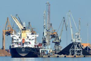 Auf dem Wasser liegt ein Industrieschiff neben mehreren Kränen