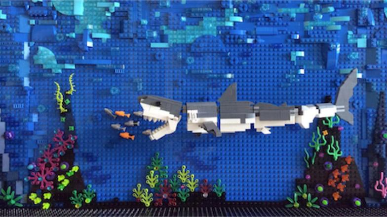 Ein kleiner Plastikdelfin wird in einem Wust aus Geisternetzen am Strand angeschwemmt.