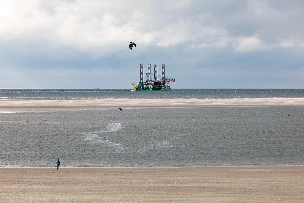 An einem Nordseestrand steht ein Kitesurfer, im Hintergrund sieht man eine Bohrinsel im Watt.
