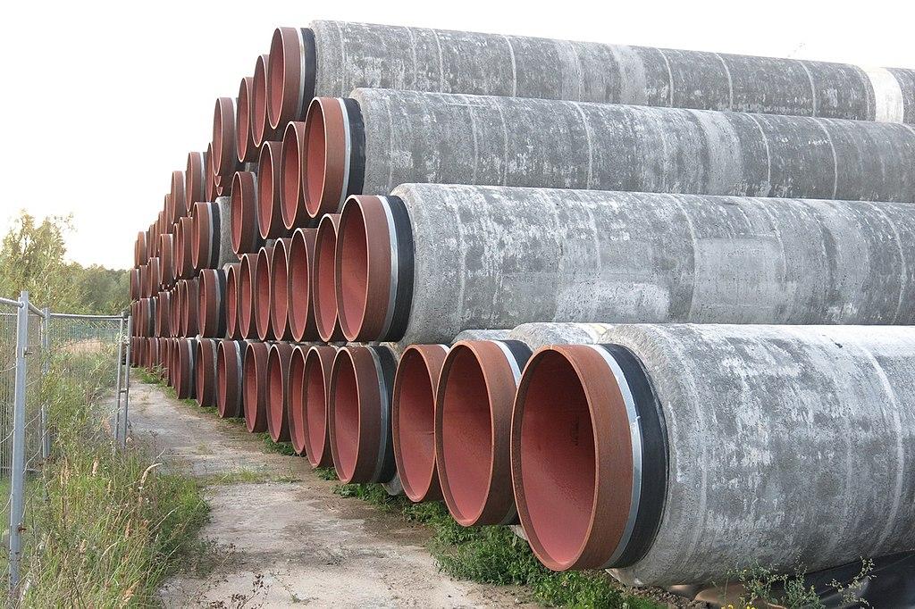 Mehrere Rohre für den Bau von Nord Stream 2 liegen gestapelt auf der Erde
