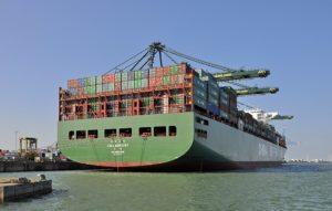 Ein großes, vollgeladenes Containerschiff liegt in einem Hafen an