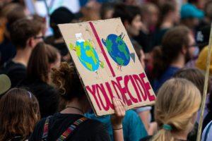 """Bei einer Demonstration hält jemand ein Schild hoch auf dem steht """"you decide"""". Mit einer hellen, glücklichen, und einer traurigen dunklen Erdkugel aufgemalt."""